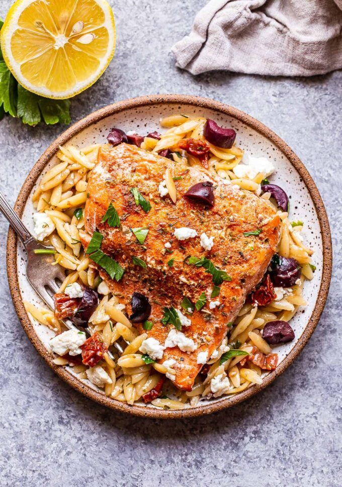 A serving of Greek Salmon and Orzo on a white plate with a half of a lemon behind the plate.