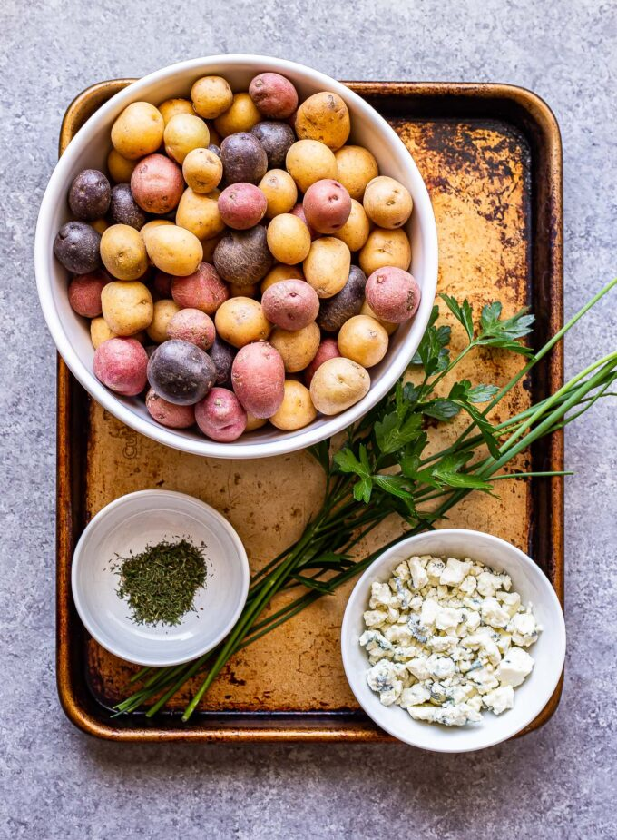 herb roasted potatoes with blue cheese ingredients on a sheet pan