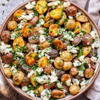 herb roasted potatoes with blue cheese in a white bowl with spoons next to it.
