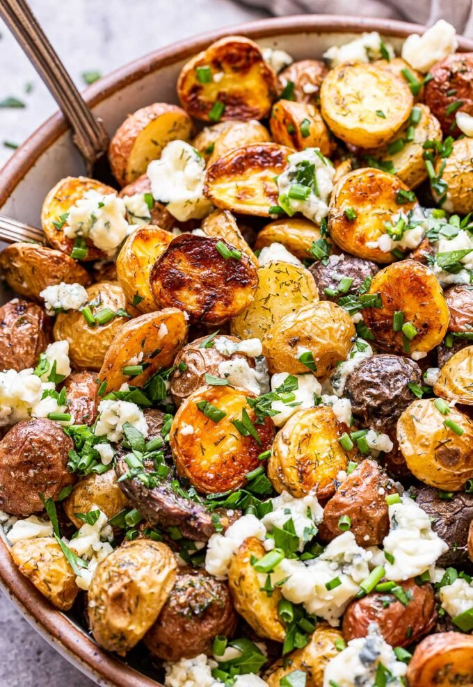 herb roasted potatoes with blue cheese in a bowl with serving spoons.