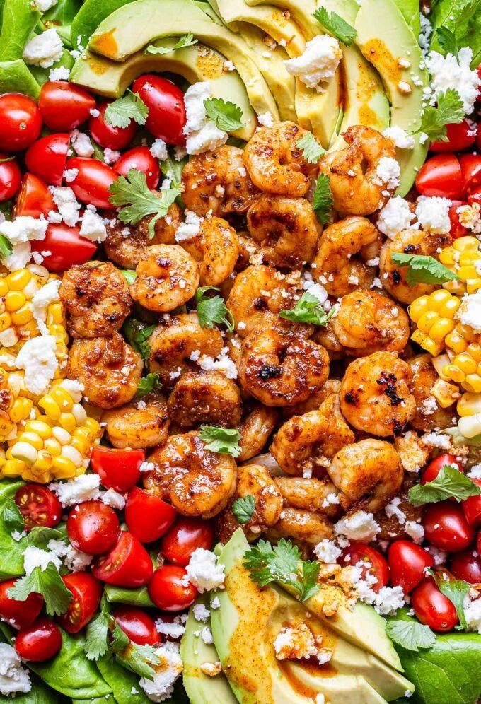 Honey Lime Shrimp Salad topped with tomatoes, avocado, corn and queso fresco.