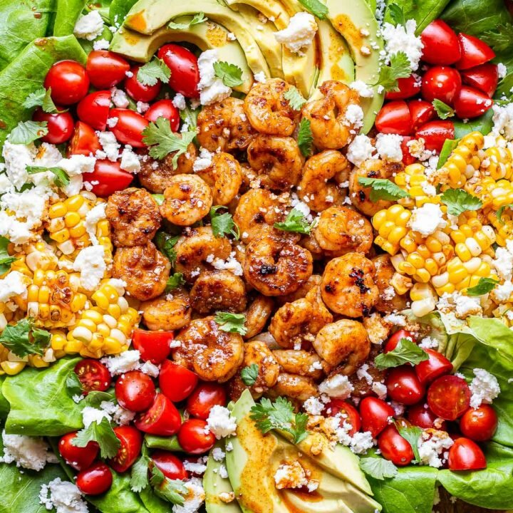 Honey Lime Shrimp Salad on a serving platter. Salad is topped with tomatoes, avocado, corn and queso fresco.