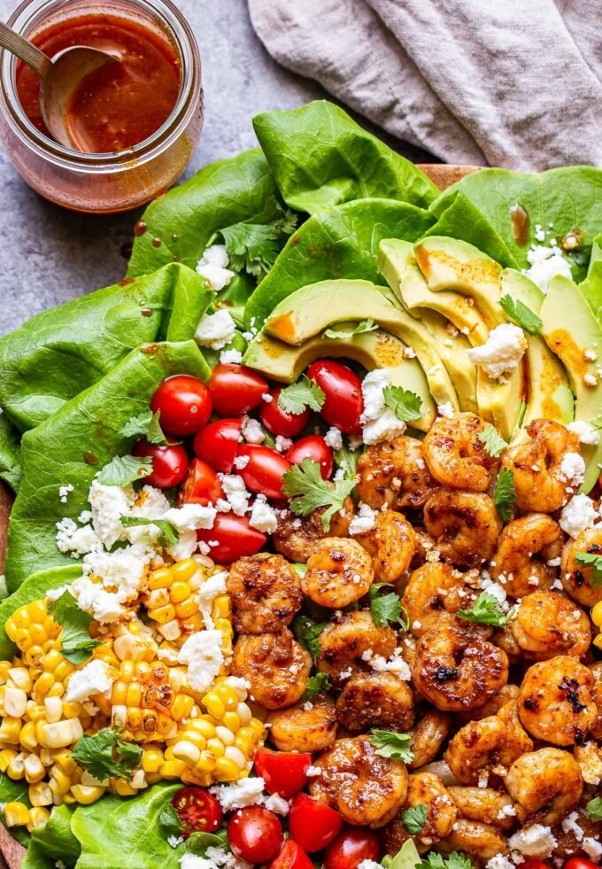 Honey Lime Shrimp Salad topped with corn, tomatoes, avocado and a jar of honey lime vinaigrette behind it.