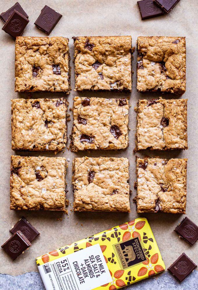 Oatmeal Chocolate Chunk Cookie Bars cut into 9 squares with a chocolate bar and chocolate squares surrounding the bars.