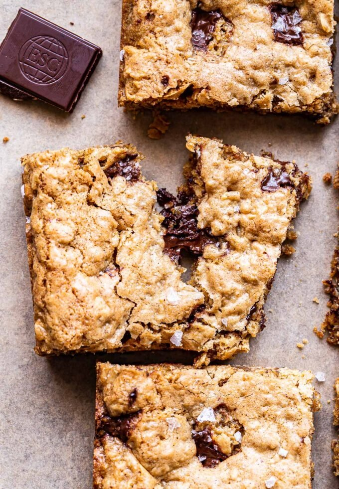 An Oatmeal Chocolate Chunk Cookie Bar broken in half and gooey melted chocolate oozing out of the middle.