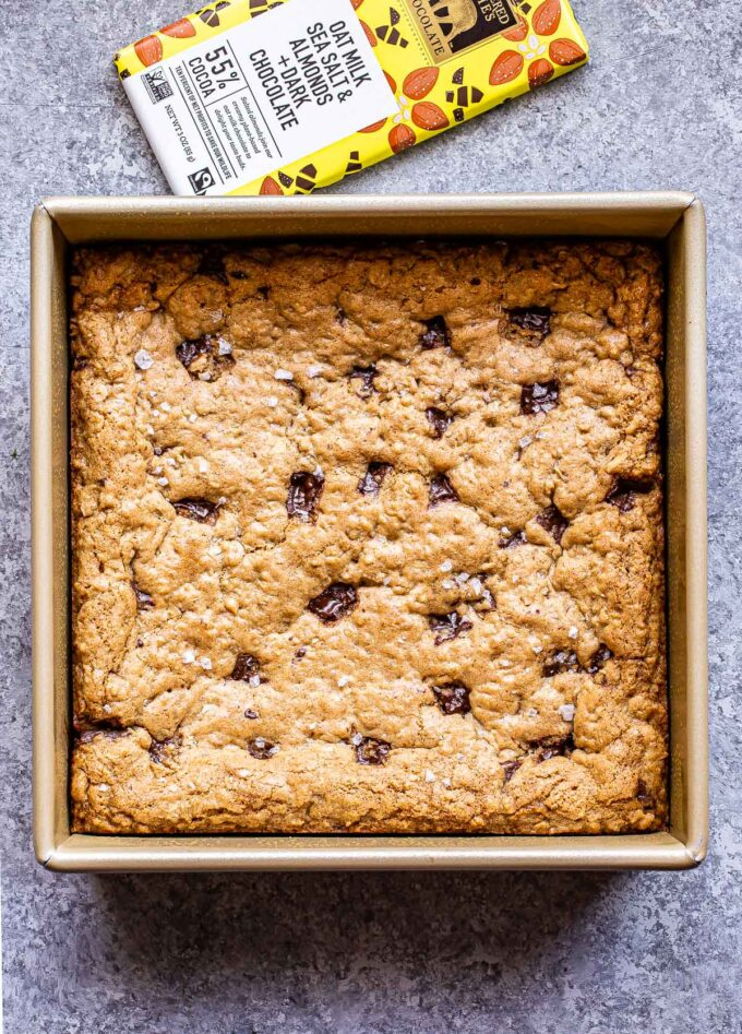 A pan of Oatmeal Chocolate Chunk Cookie Bars with a chocolate bar behind it.