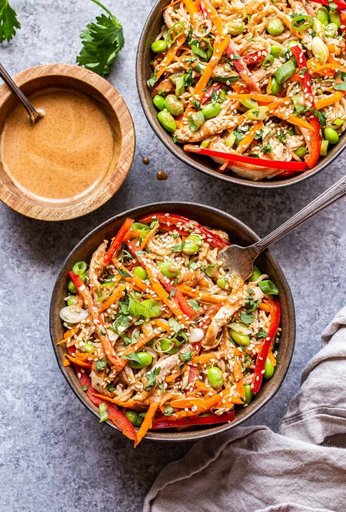 two Sesame Chicken Noodle Bowls with a small bowl of almond butter sauce next to them.