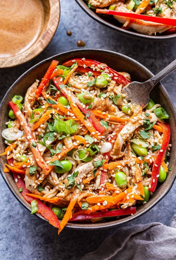 Gray bowl with Sesame Chicken Noodles topped with red bell peppers, shredded carrot and edamame.