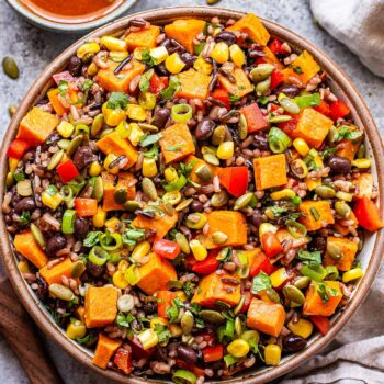 Southwest Sweet Potato, Black Bean, Wild Rice Salad in a white bowl with chili lime vinaigrette behind it.