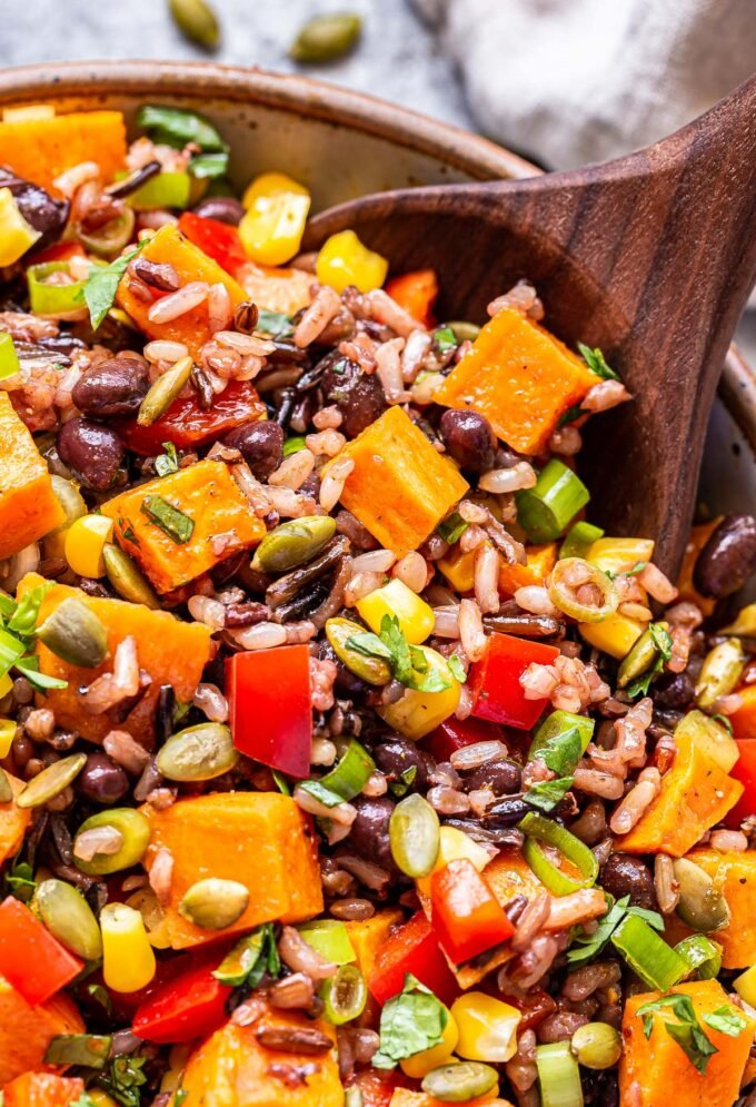 Southwest Sweet Potato, Black Bean, Wild Rice Salad with a wooden serving spoon scooping some up from the bowl.