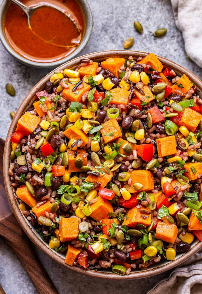 Southwest Sweet Potato, Black Bean, Wild Rice Salad with corn and cilantro in a bowl with a bowl of vinaigrette behind it.