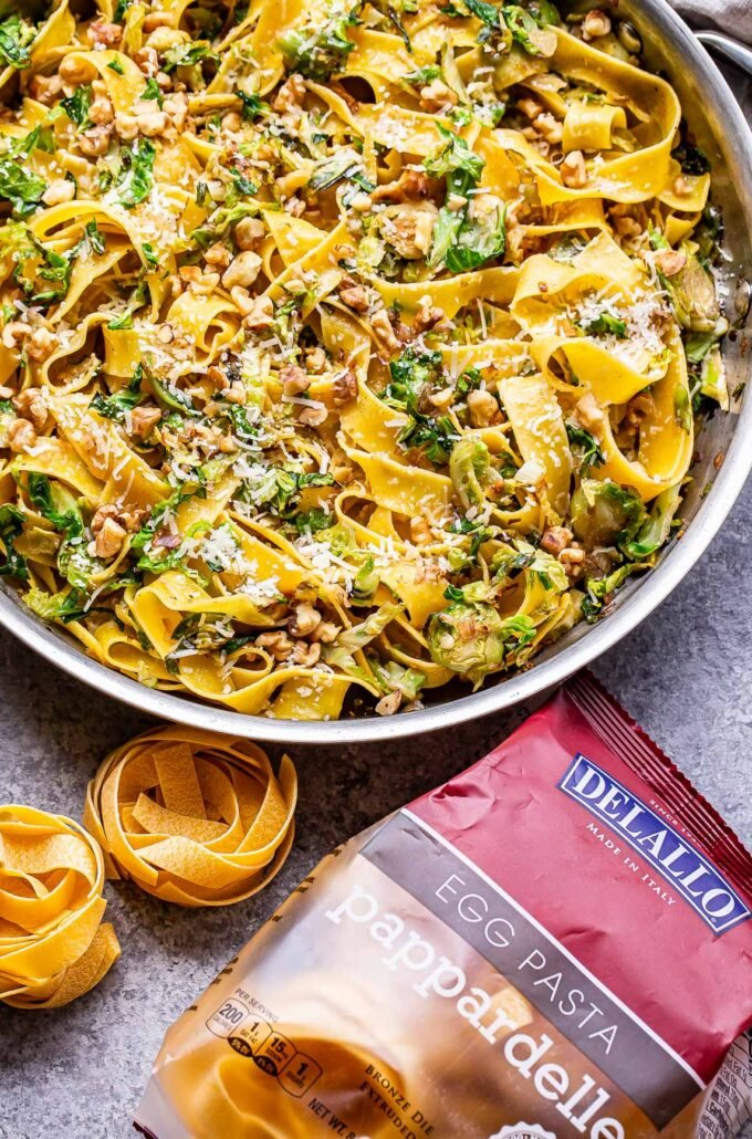 brown butter brussels sprouts pasta in a skillet with a bag of pappardelle pasta in front of it.