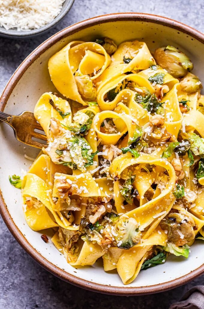 brown butter brussels sprouts pasta in a white bowl with a fork