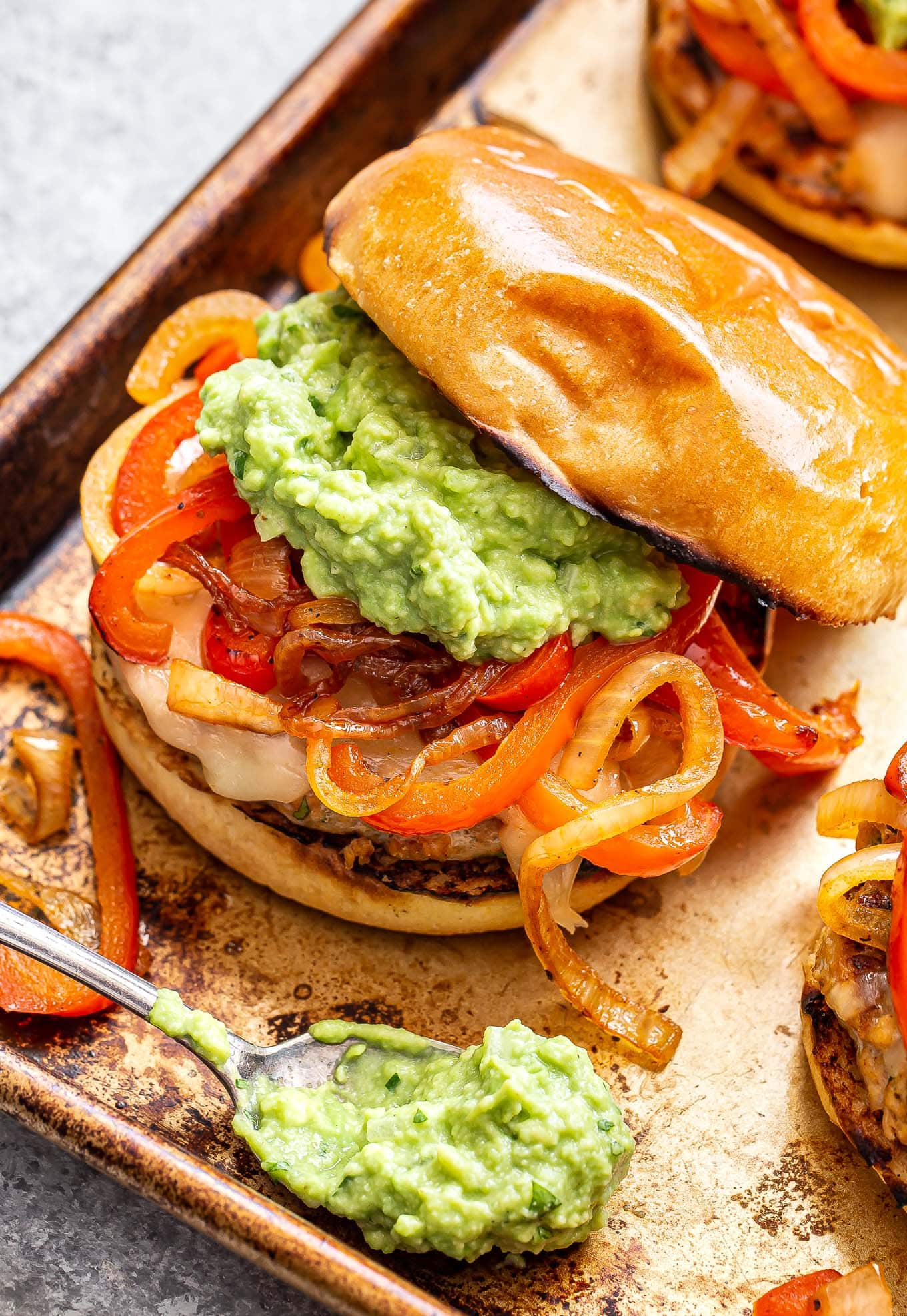 Chicken Fajita Burger topped with peppers, onions and guacamole with a spoon of guacamole in front of the burger.