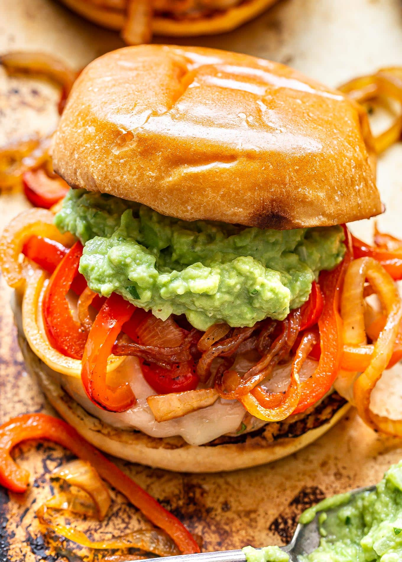 Chicken Fajita Burger topped with peppers, onions and guacamole.