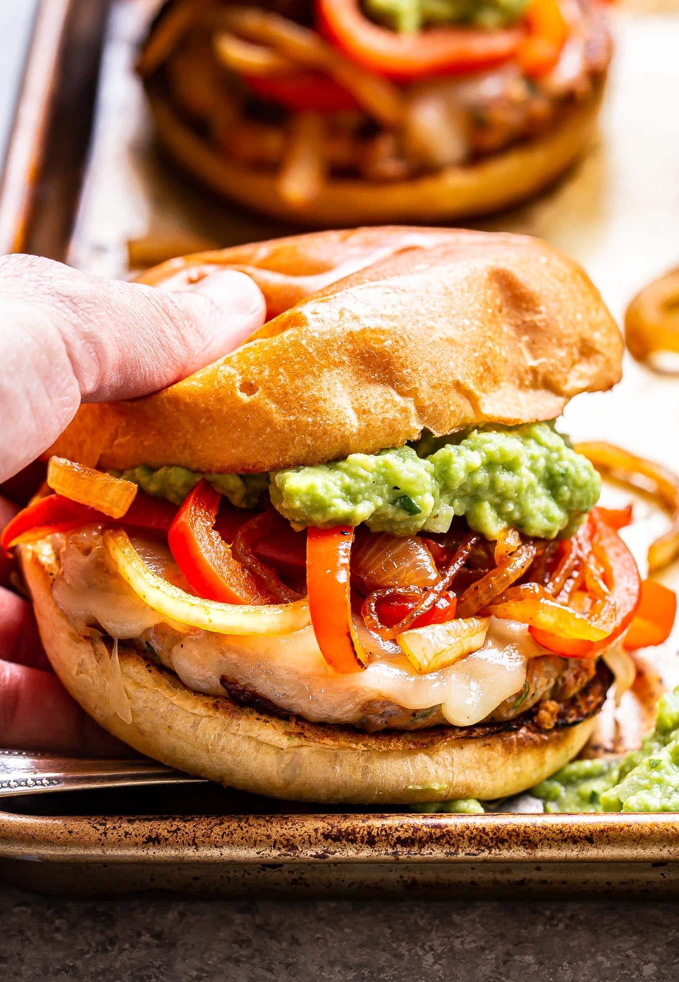 Hand picking up a Chicken Fajita Burger.