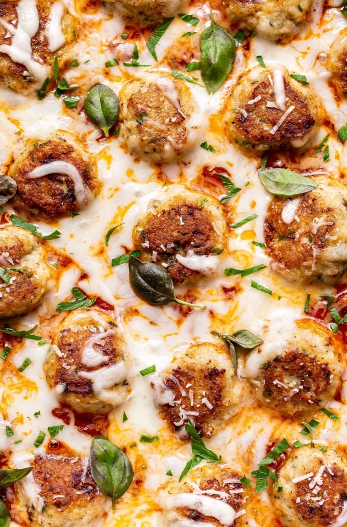 closeup photo of Chicken Parmesan Meatballs covered in melted cheese.
