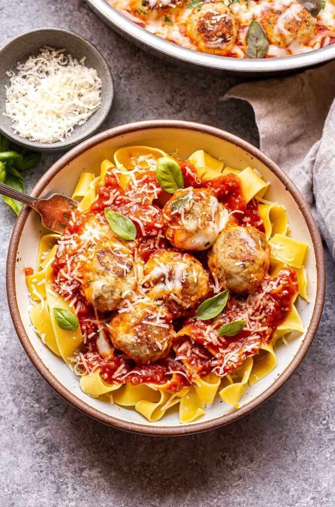 Chicken Parmesan Meatballs on top of pasta in a white bowl with a fork