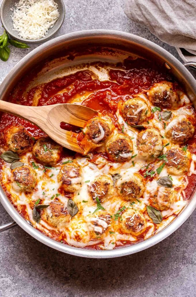 Chicken Parmesan Meatballs in a skillet with a wooden spoon.