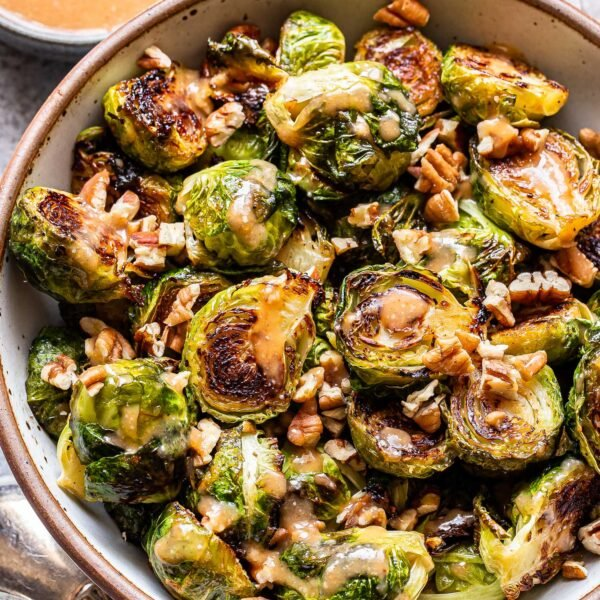 Miso roasted brussels sprouts in a white bowl with a small bowl of dressing behind them.