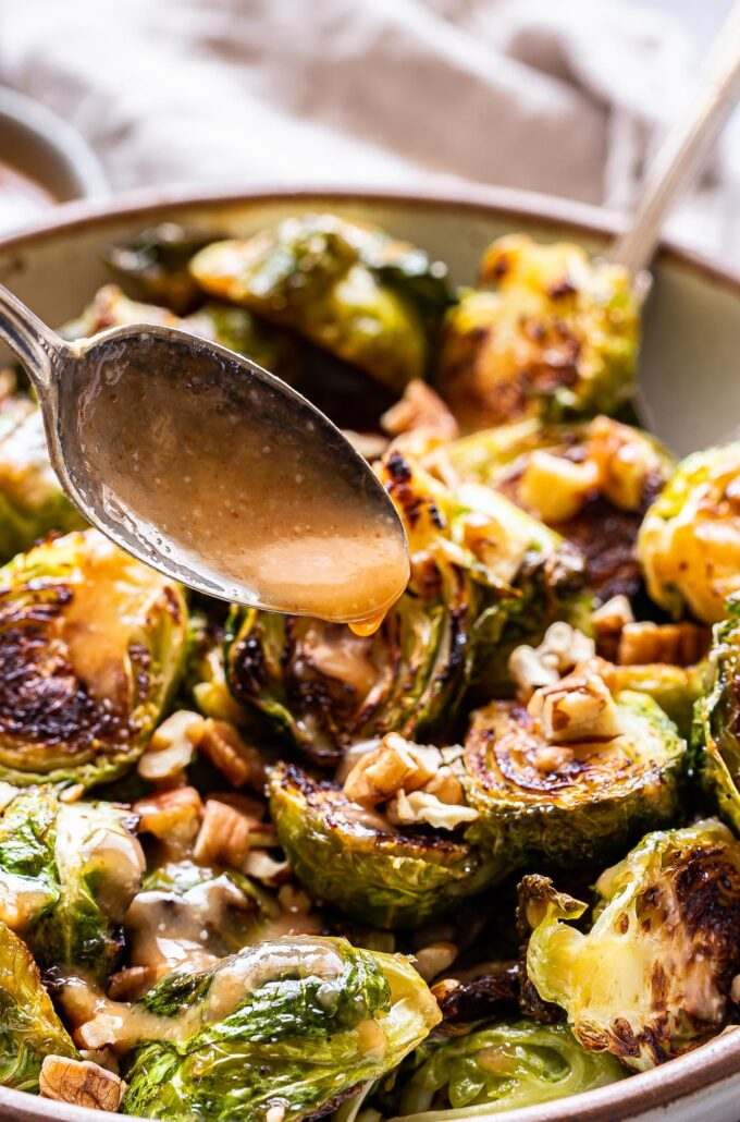 spoon drizzling dressing on top of Miso roasted brussels sprouts