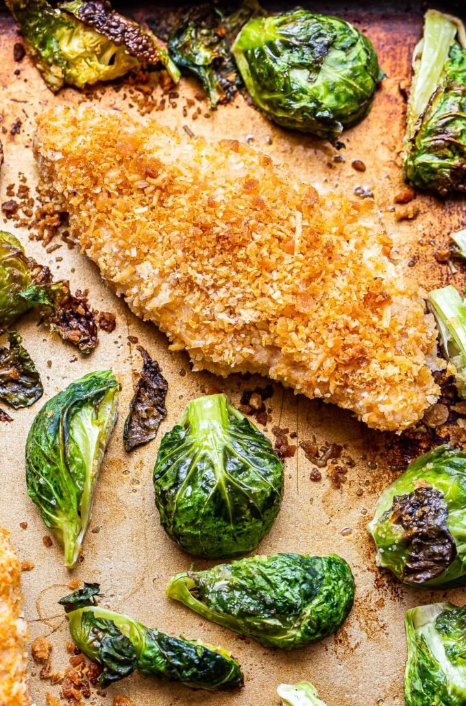 Parmesan chicken and brussels sprouts on a sheet pan.