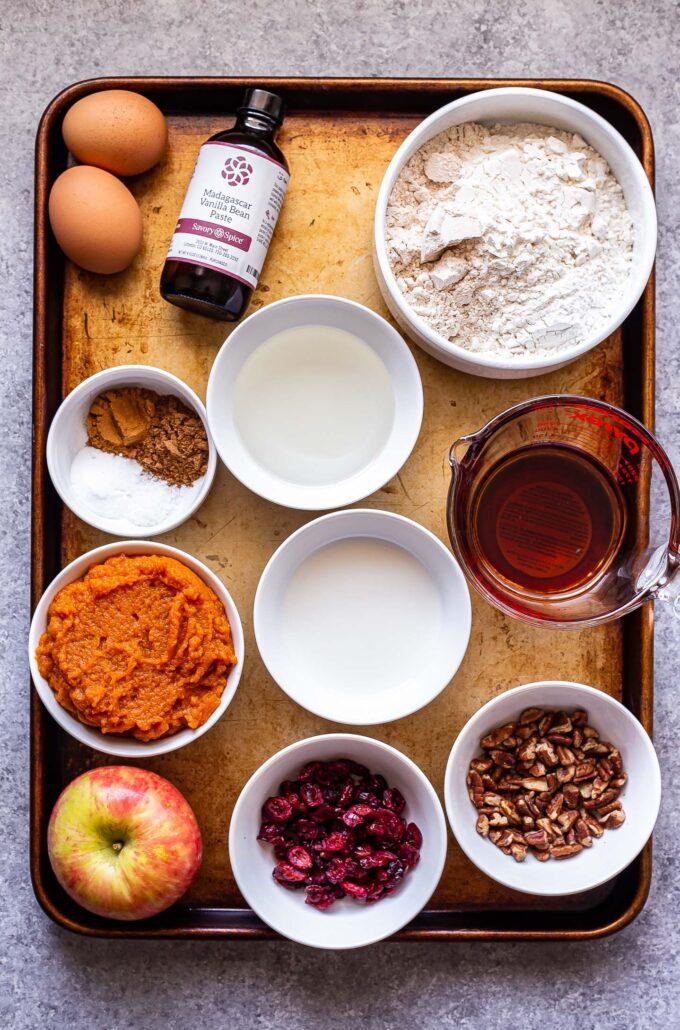 ingredients used to make pumpkin apple muffins on a sheet pan