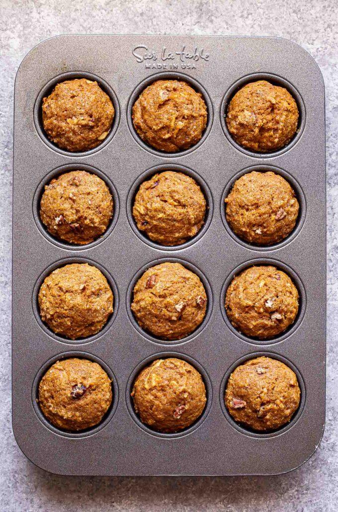 12 pumpkin apple muffins in a muffin pan