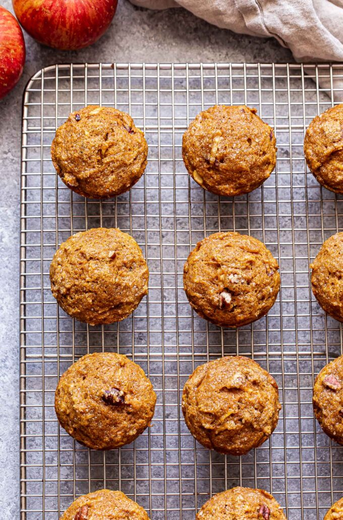pumpkin apple muffins on a wire cooling rack with apples behind the rack.