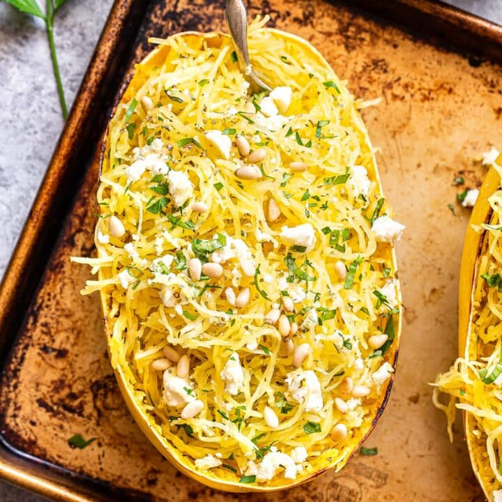 Half of a Spaghetti Squash with Feta and Herbs on a sheet pan with a fork in it