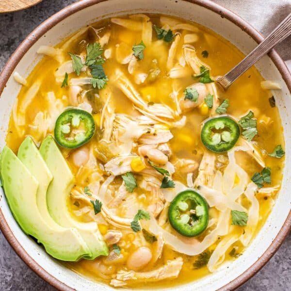 White Chicken Chili in a white bowl with a spoon and a small bowl of lime wedges behind it.