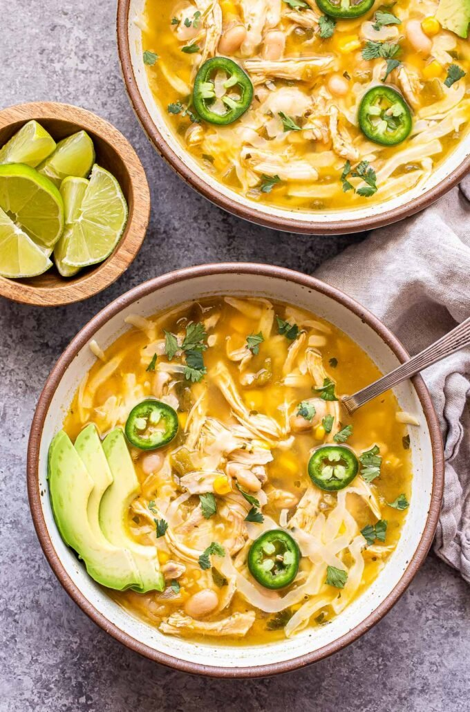 two bowls of White Chicken Chili with a small bowl of lime wedges.