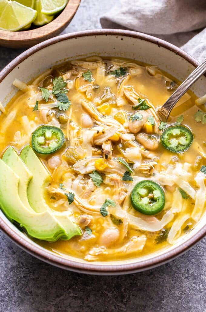 White Chicken Chili in a white bowl with a spoon. Topped with cheese