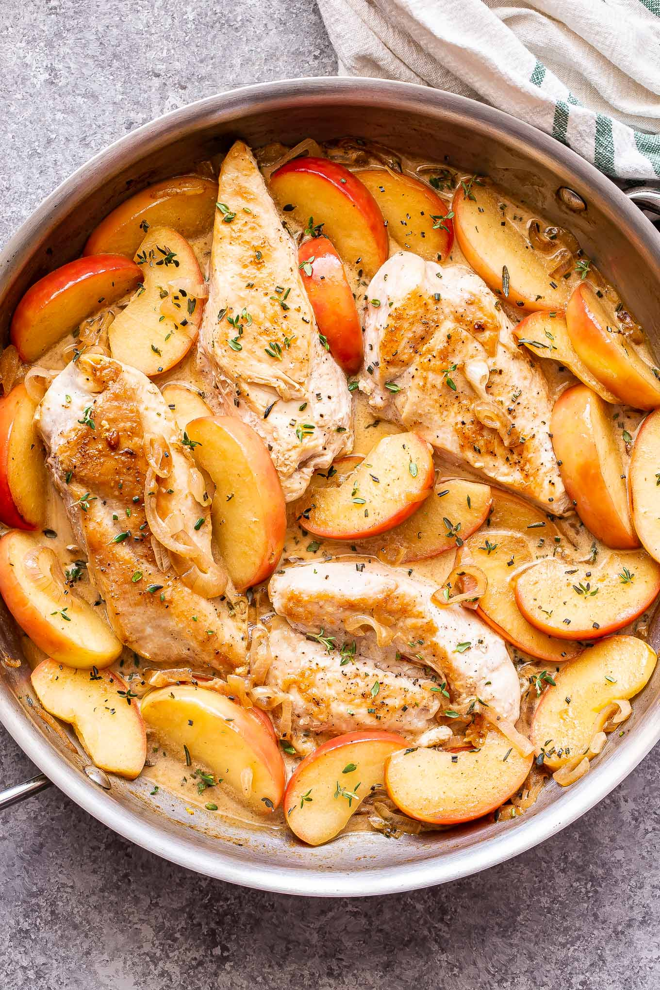 stainless steel skillet with Apple cider chicken in it.