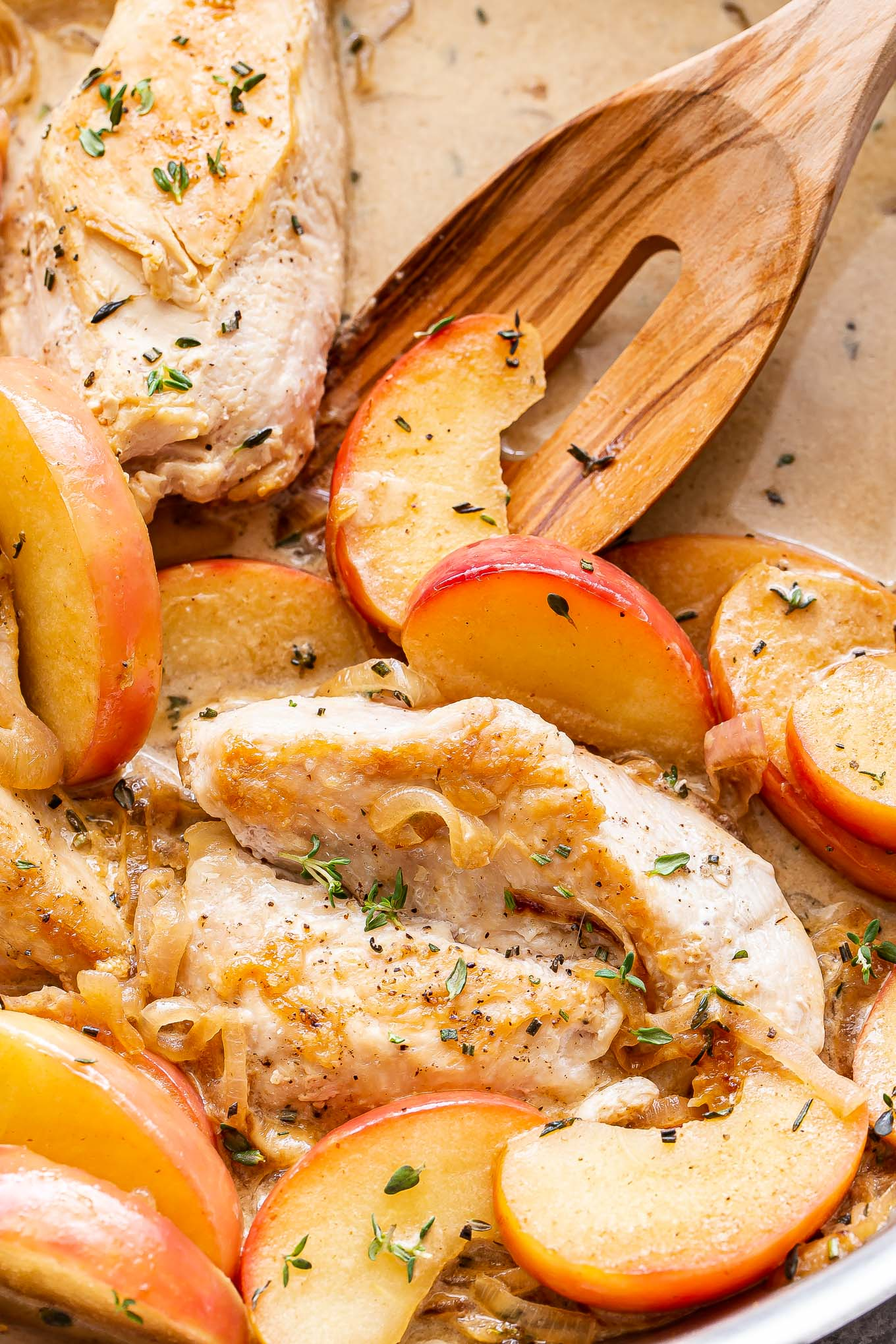 Apple cider chicken with a wooden spoon in the skillet.