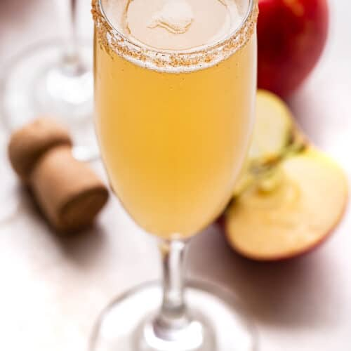 Apple Cider Mimosa with a champagne cork and apples behind it.