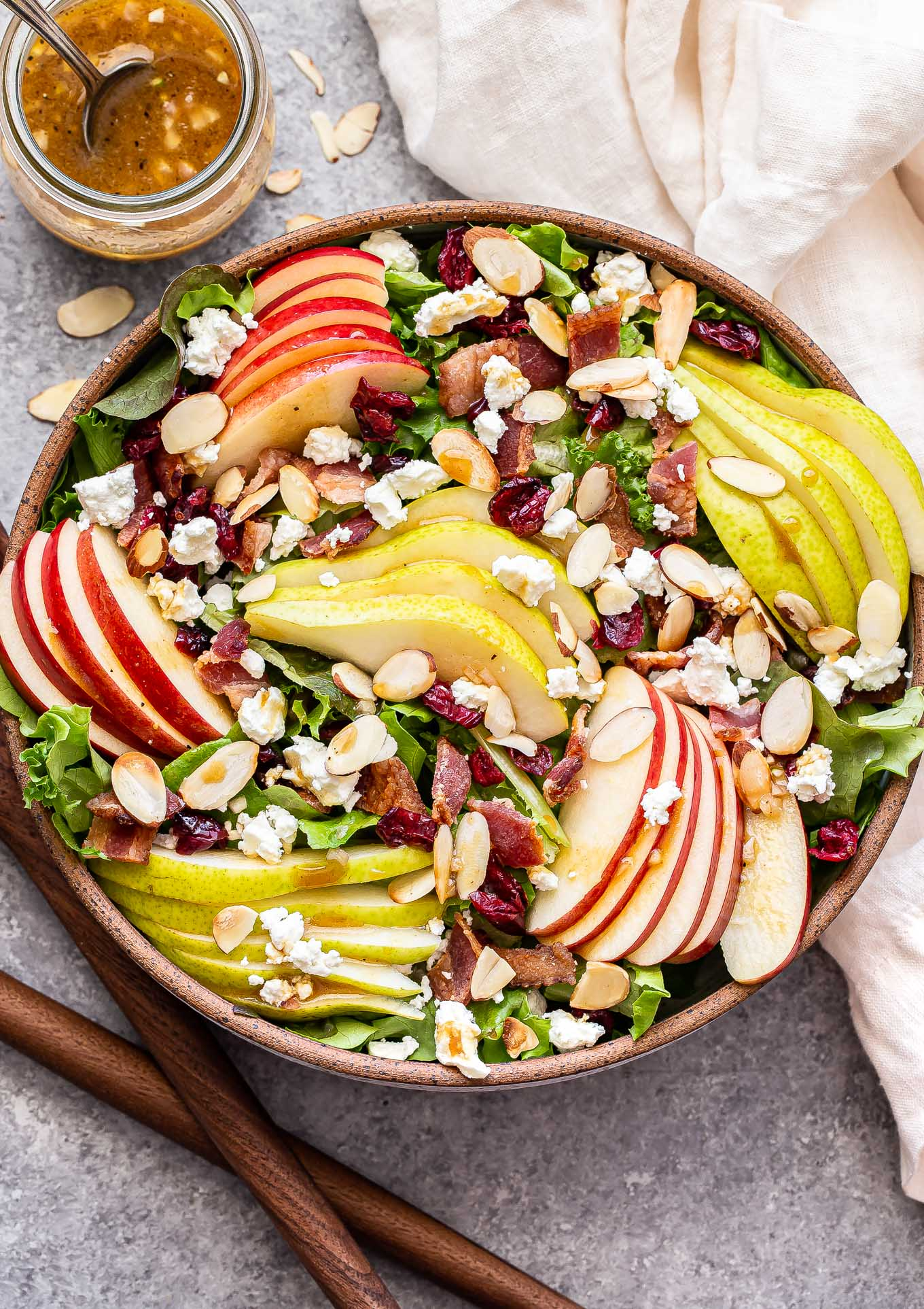 Autumn Apple and Pear Salad in a serving bowl with wooden spoons next to it and cider vinaigrette behind it.