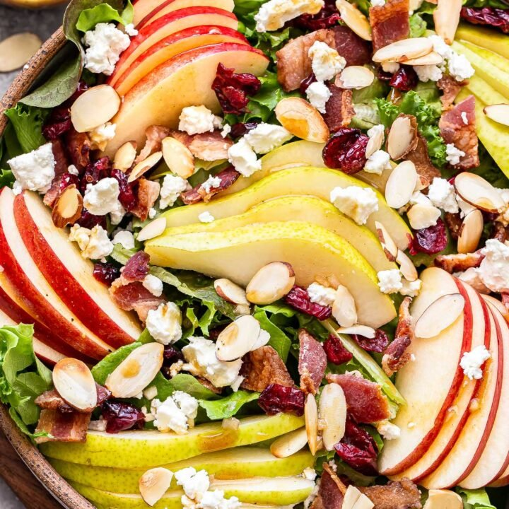 Autumn Apple and Pear Salad in a serving bowl with a jar of vinaigrette behind it.