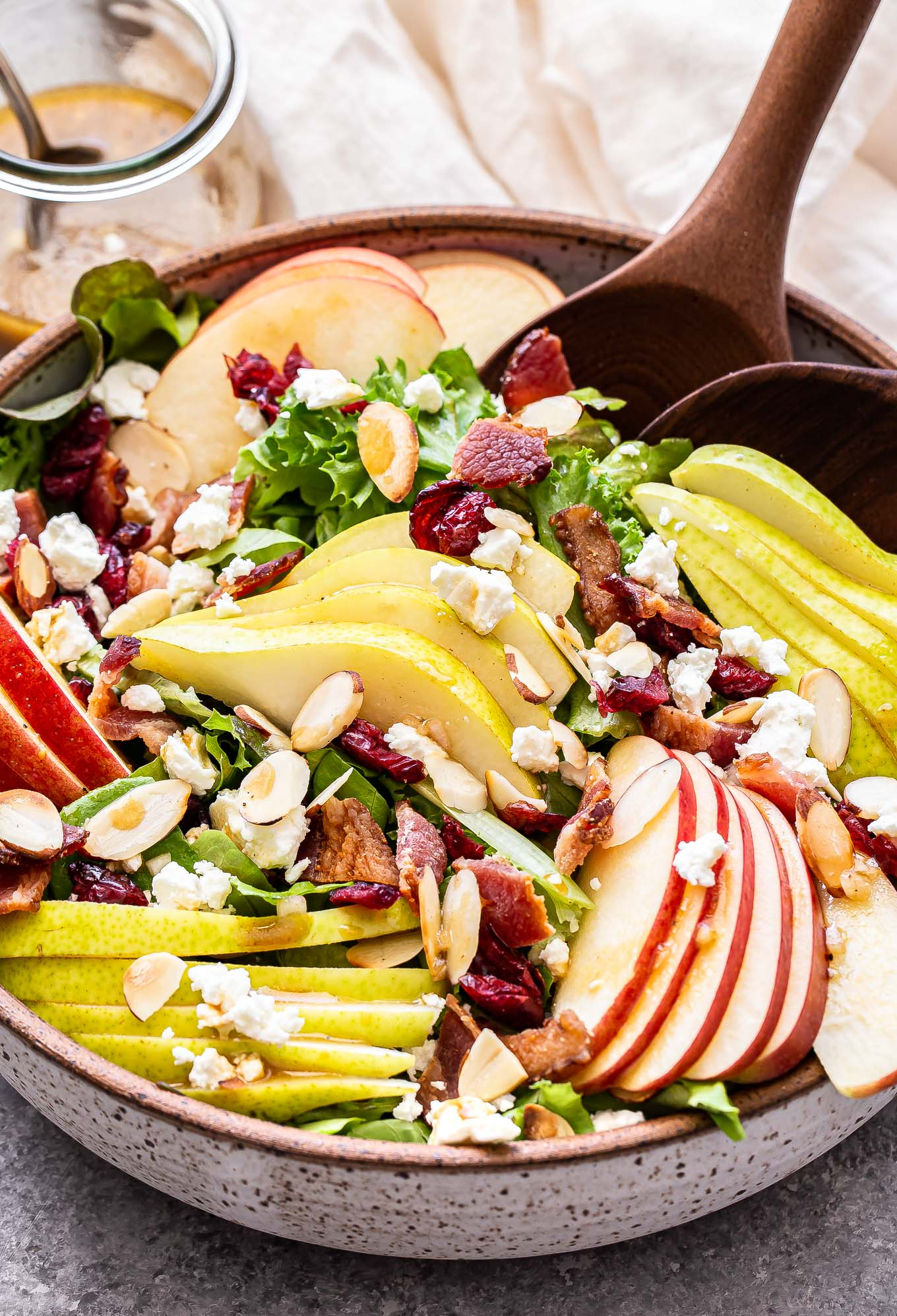 Autumn Apple and Pear Salad in a white serving bowl with wooden spoons