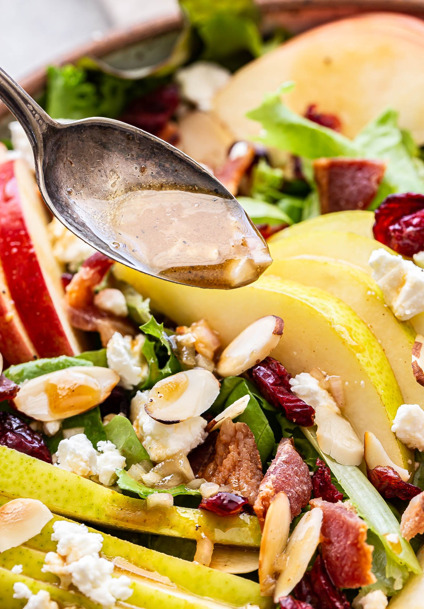 spoon pour vinaigrette over the Autumn Apple and Pear Salad