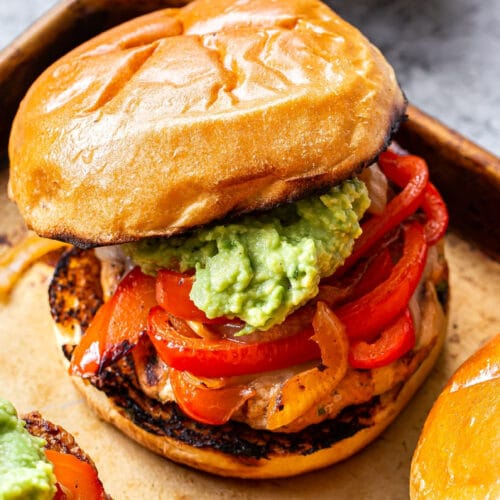 Chicken Fajita Burger topped with peppers, onions and guacamole with a bowl of guacamole behind the burger.