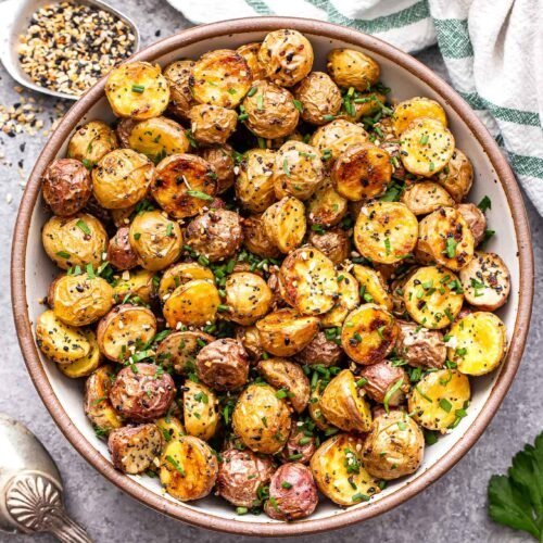Everything Bagel Roasted Potatoes in a bowl with a spoon of the seasoning behind them.
