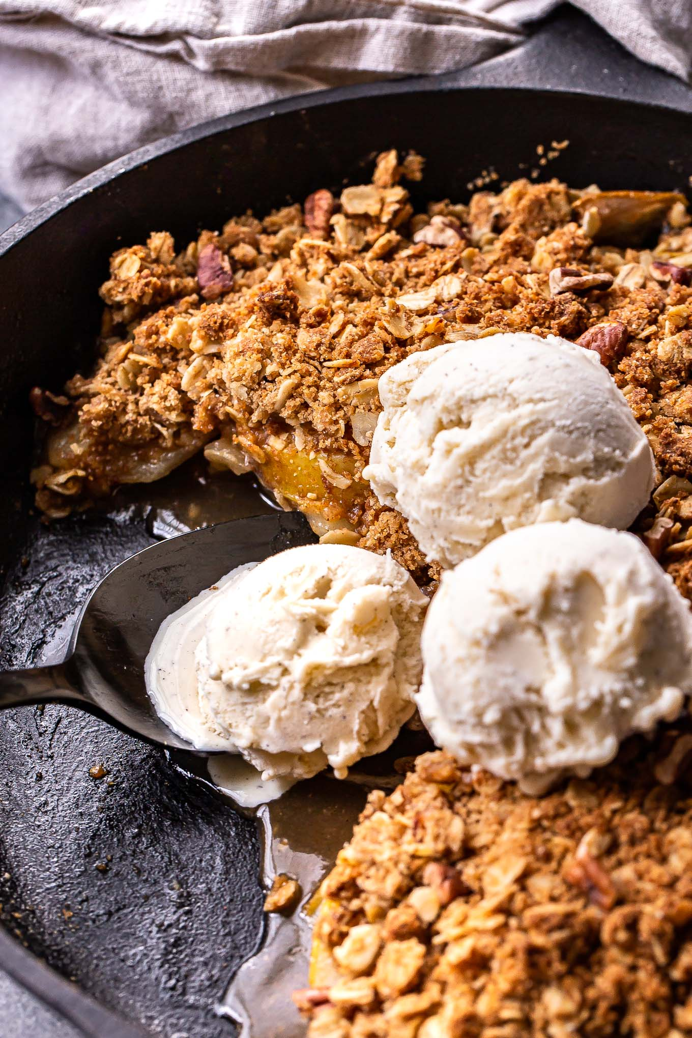 Pear Crisp with a portion scooped out and 3 scoops of vanilla ice cream on top of it.