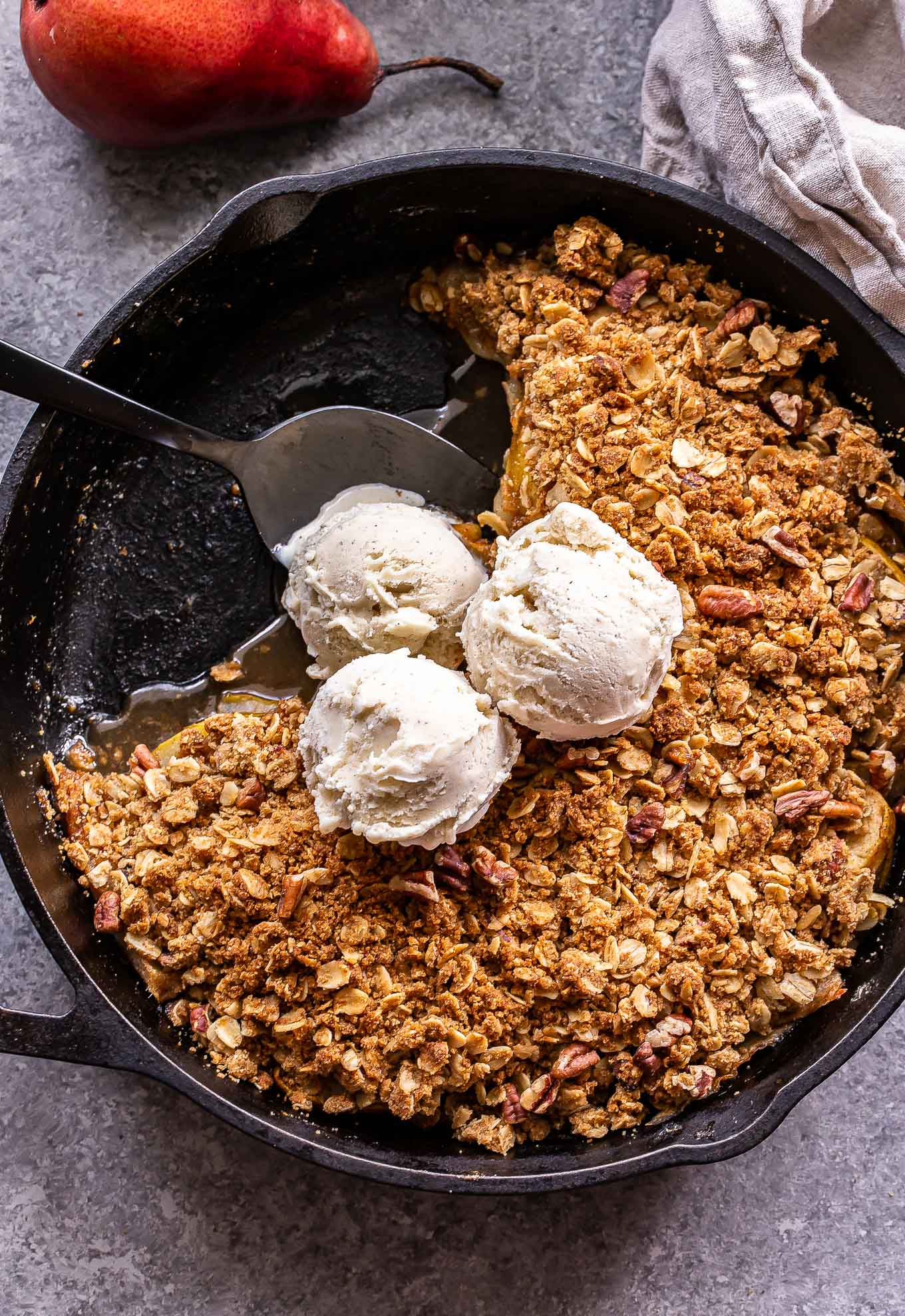 Pear Crisp in a cast iron skillet topped with vanilla ice cream.