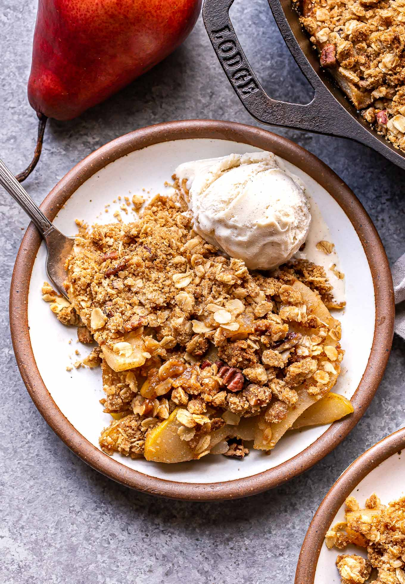 Pear Crisp on a white plate with a fork and a scoop of vanilla ice cream. A red pear is behind the plate.